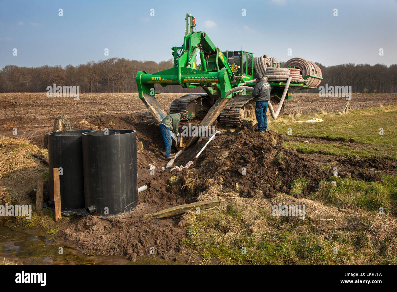 Contractors working with drainage trencher / tile plow on farmland - Stock Image