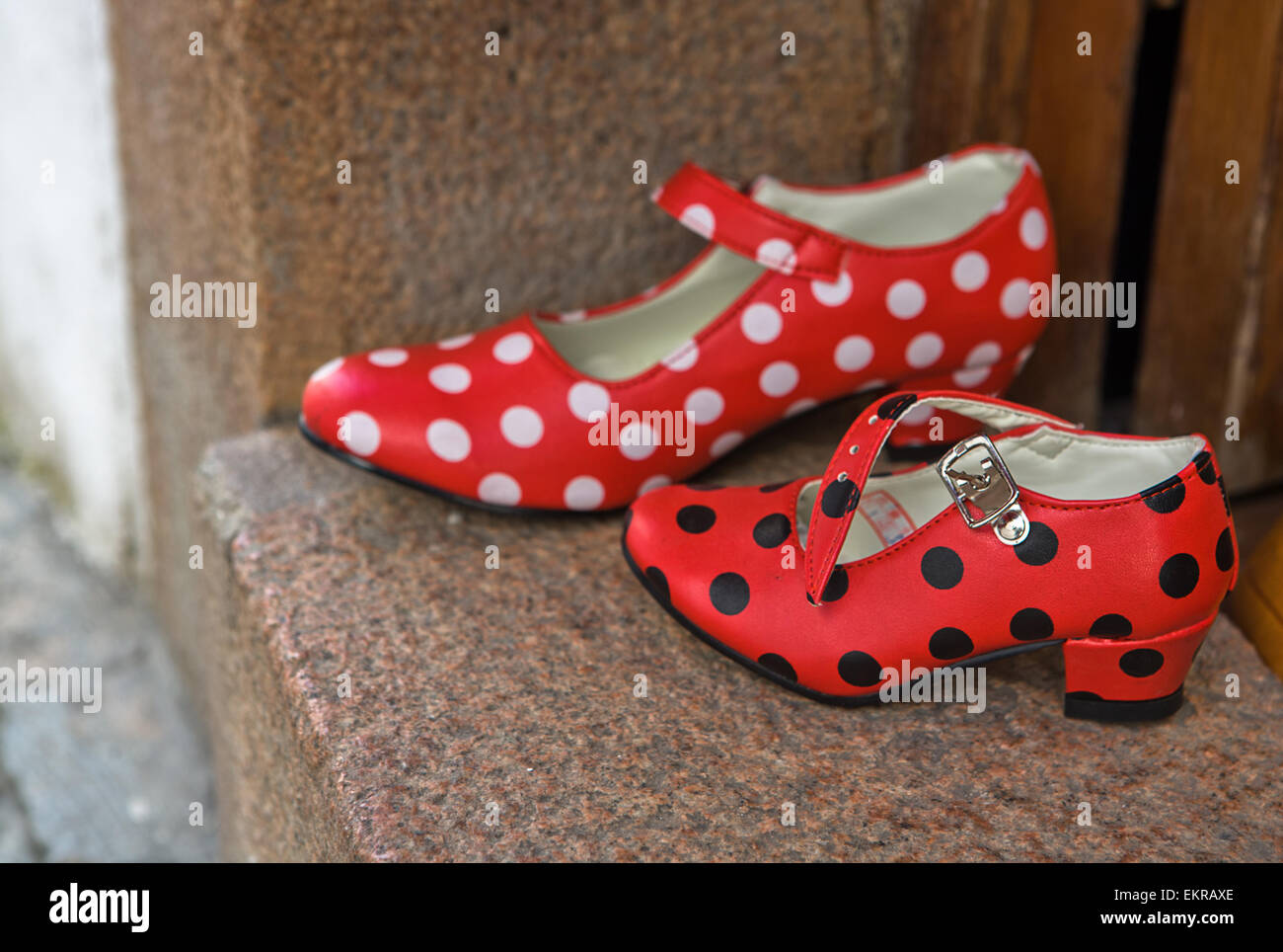 Gypsy red shoes with polka dot spots in street market - Stock Image