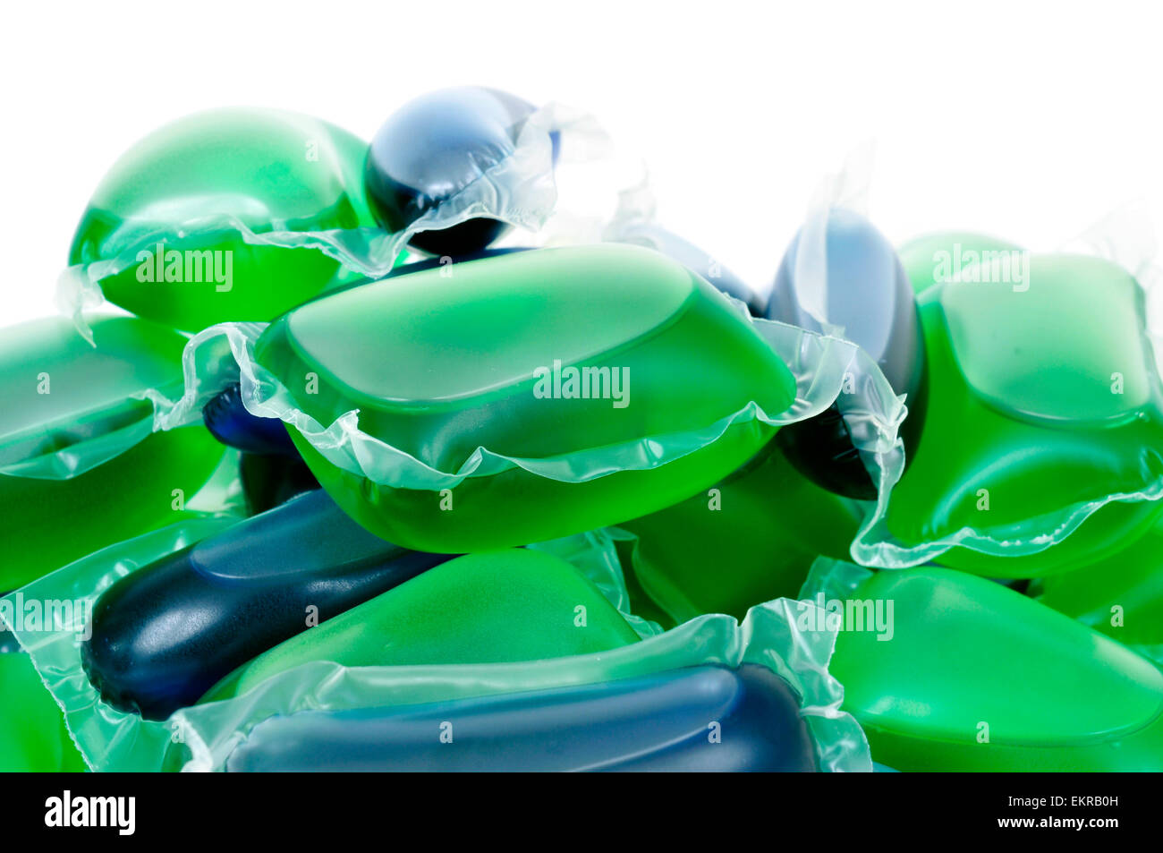 closeup of a pile of liquid laundry detergent sachets on a white background - Stock Image