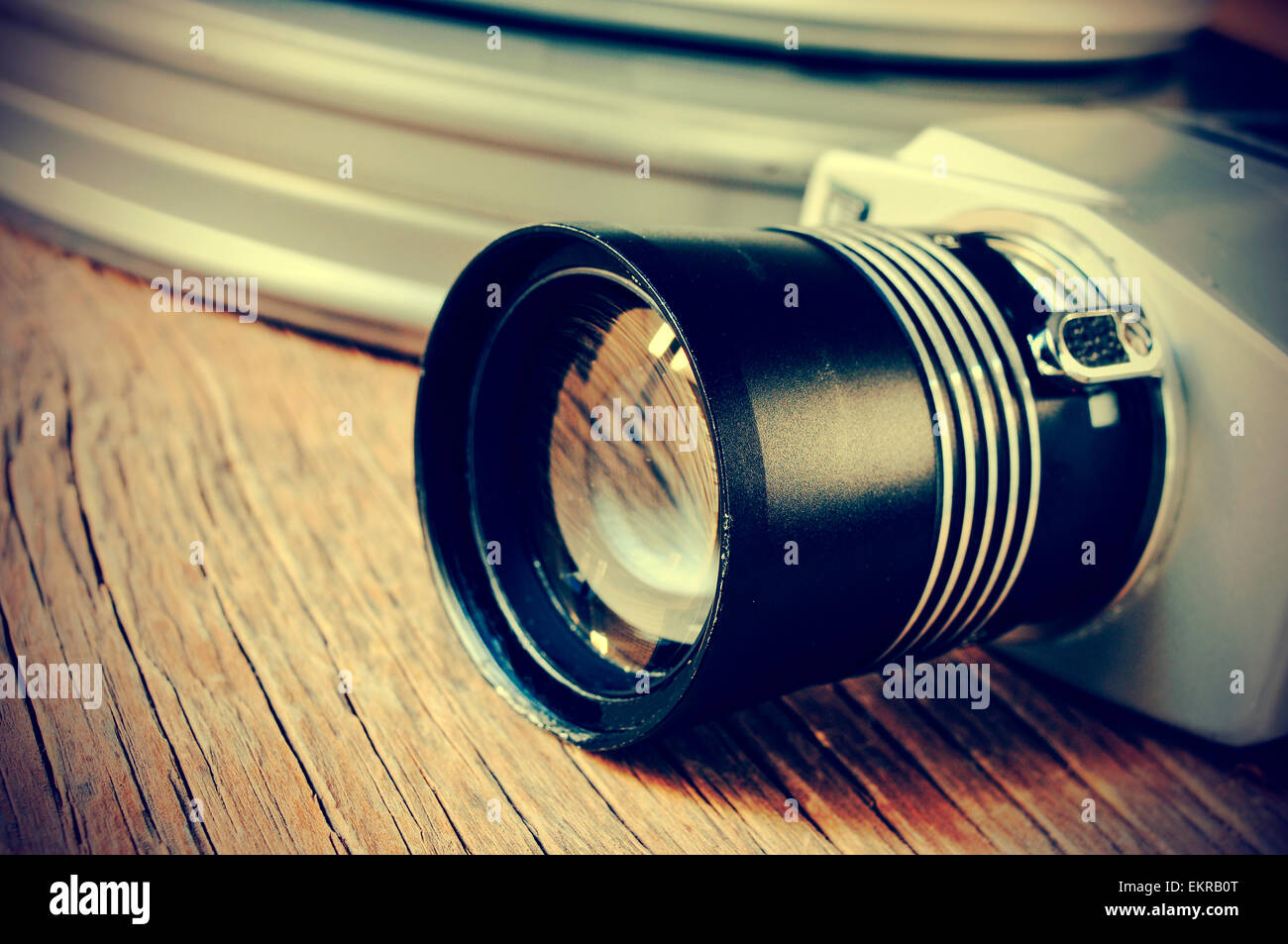 closeup of a retro film camera and some metal movie film reel canisters on a rustic wooden surface, filtered and - Stock Image