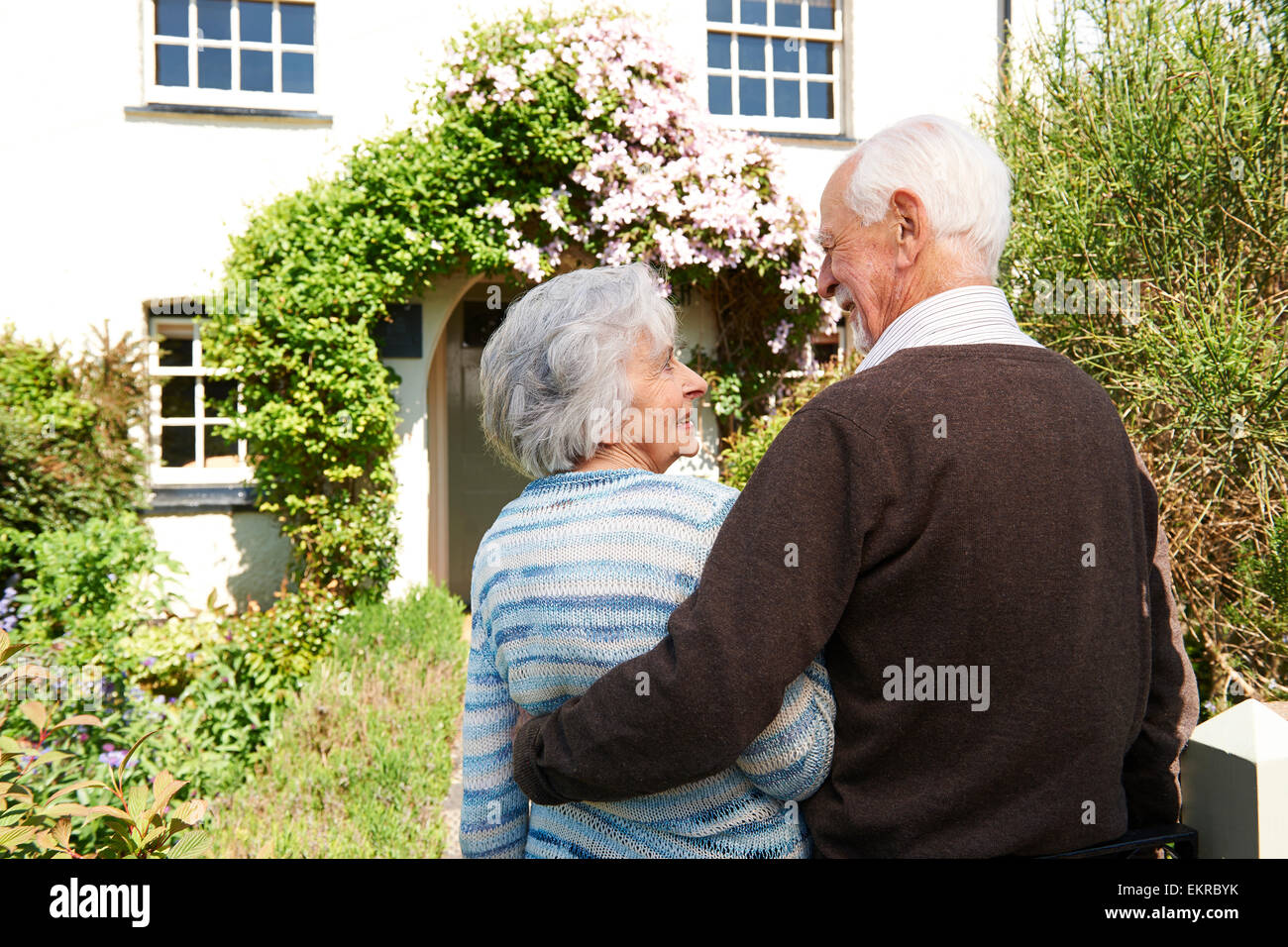 Rear View Of Senior Couple Outside Pretty Cottage - Stock Image
