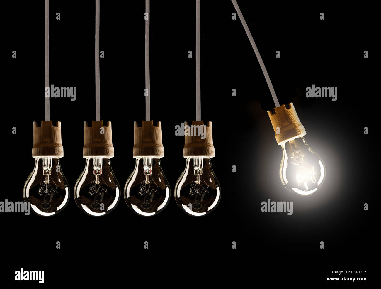 Light bulbs in row with single one in motion and shinning, isolated on black background - Stock Image