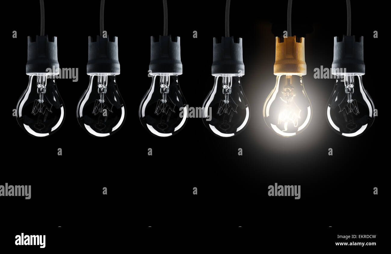 Light bulbs in row with single one shinning, isolated on black background - Stock Image