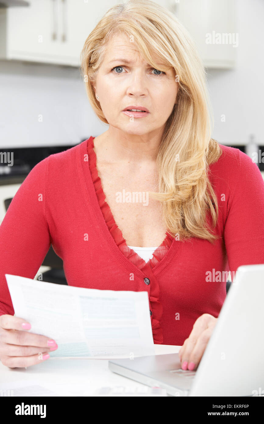 Worried Mature Woman Looking Reviewing Finances At Home - Stock Image