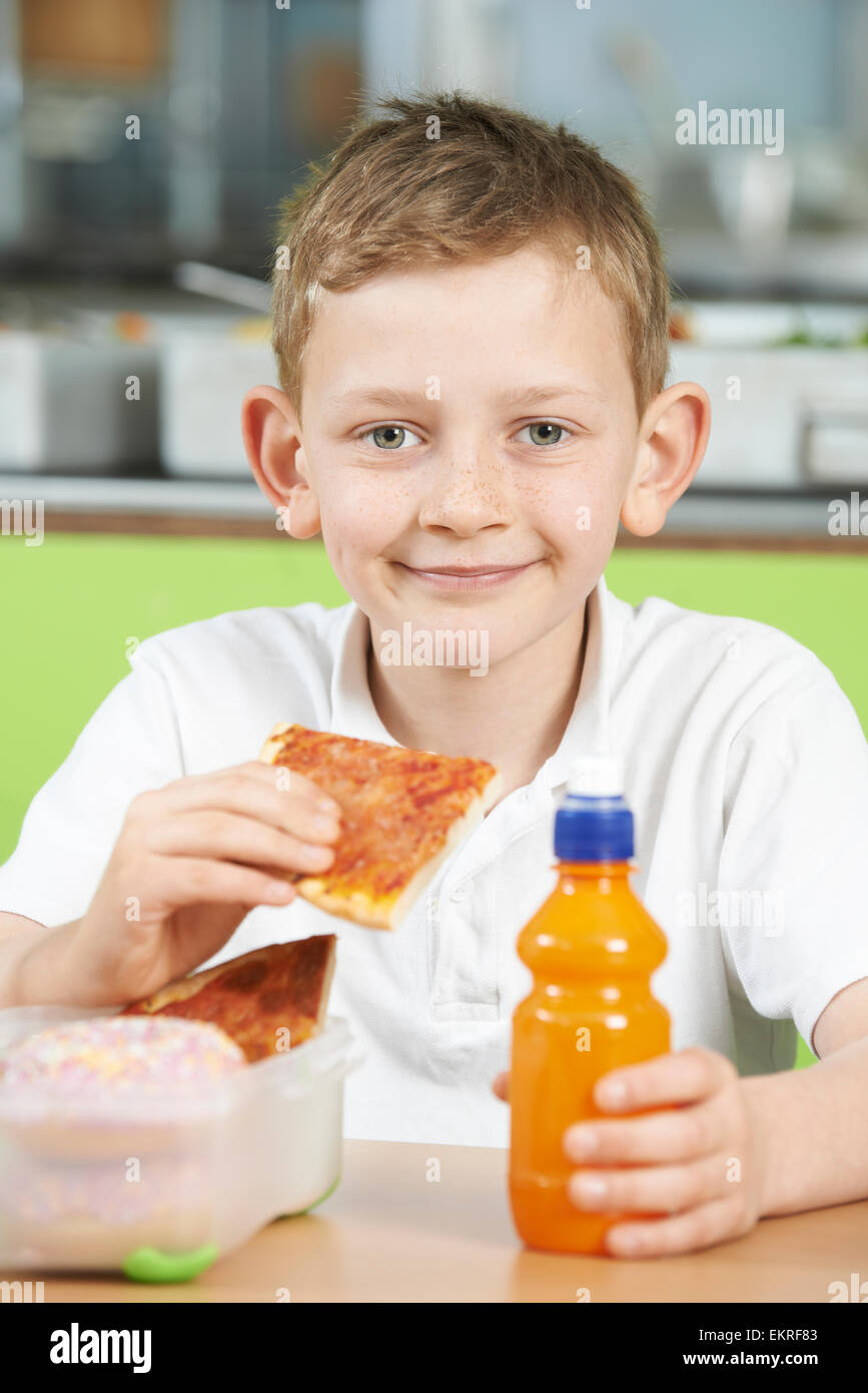 Male Pupil Sitting At Table In School Cafeteria Eating Unhealthy Packed Lunch Stock Photo