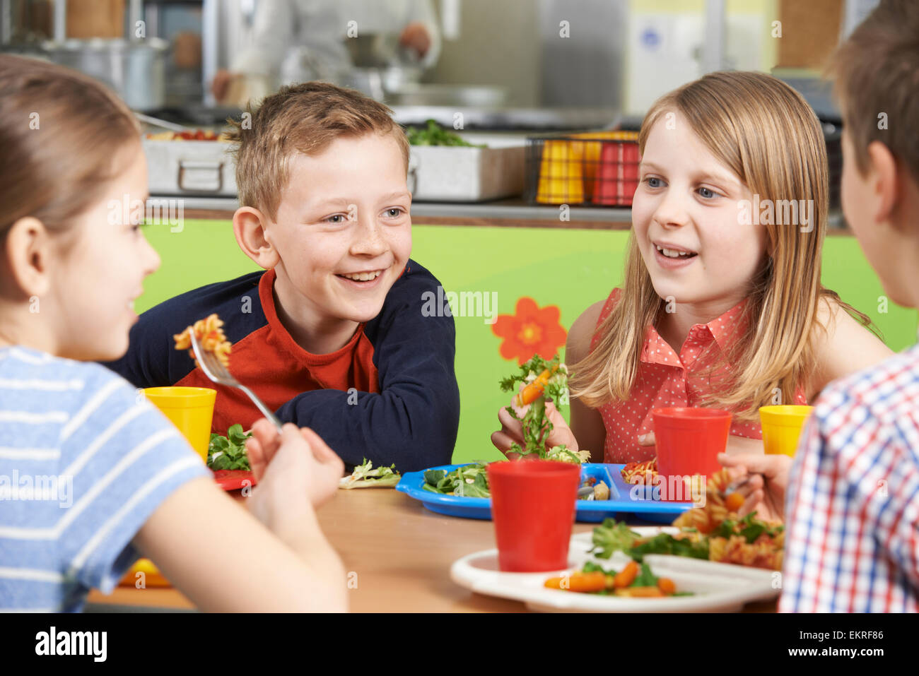 Group Of Pupils Sitting At Table In School Cafeteria Eating Lunch - Stock Image
