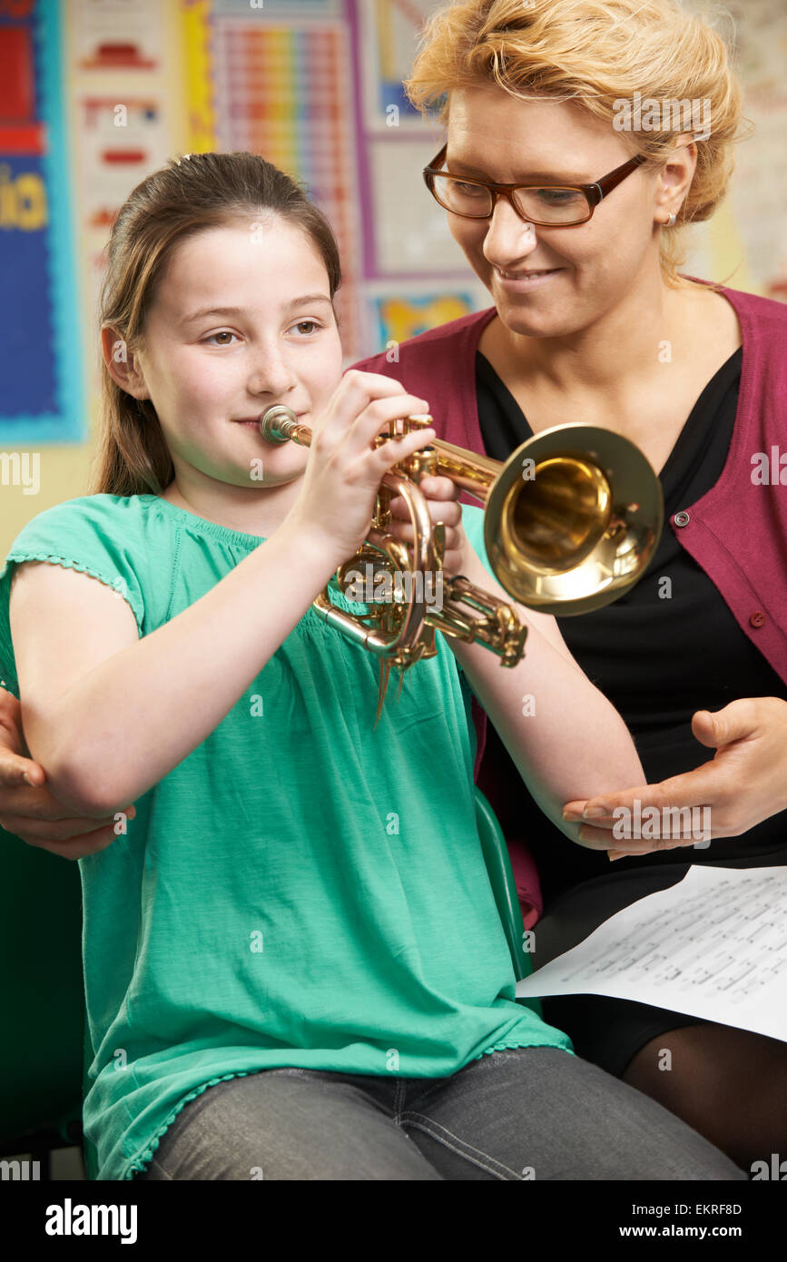 Teacher Helping Pupil To Play Trumpet In Music Lesson Stock