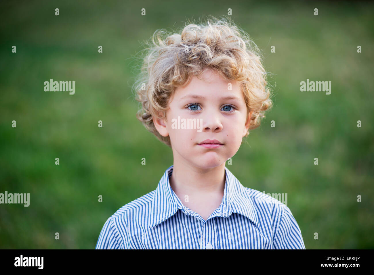 Portrait Of A Young Boy With Blond Curly Hair And Blue