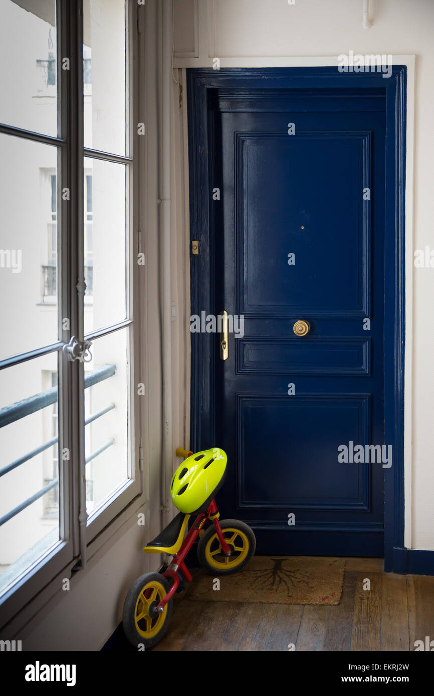 A blue door with a child's balance bicycle (no pedals) and helmet inside an apartment building hallway in Paris, Stock Photo