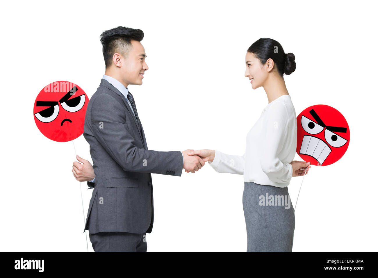 Business person shaking hands with angry emoticon faces behind their backs - Stock Image