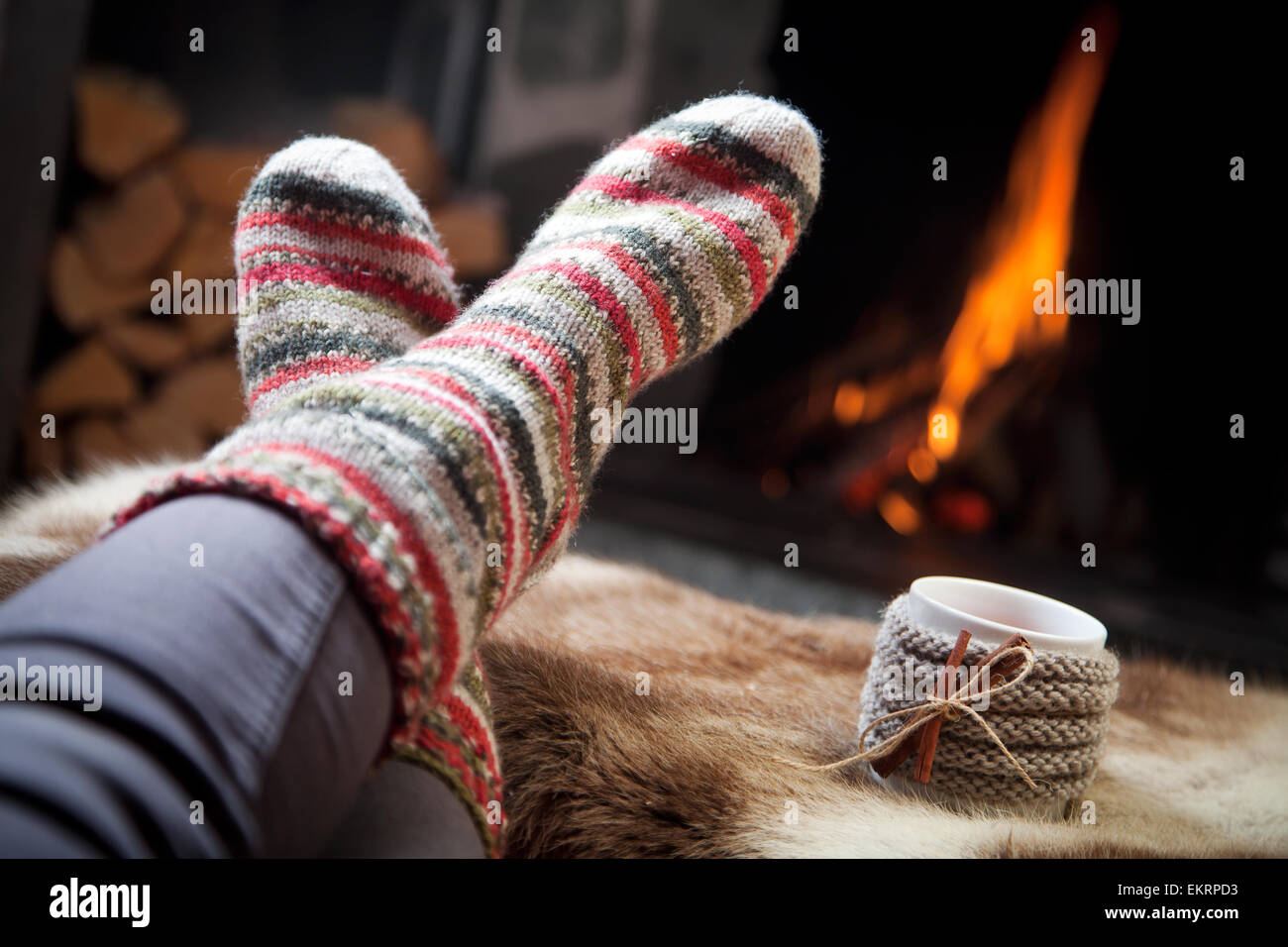 Warming up by the fireplace - Stock Image