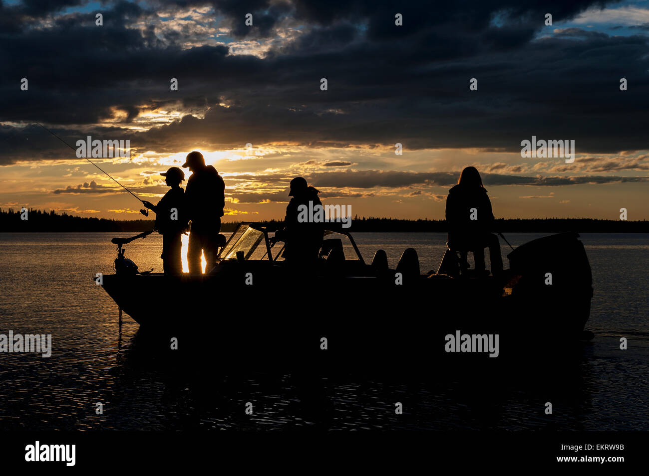 Silhouette of a family fishing from their motorboat on a lake at sunset in Northern Ontario; Ontario, Canada - Stock Image