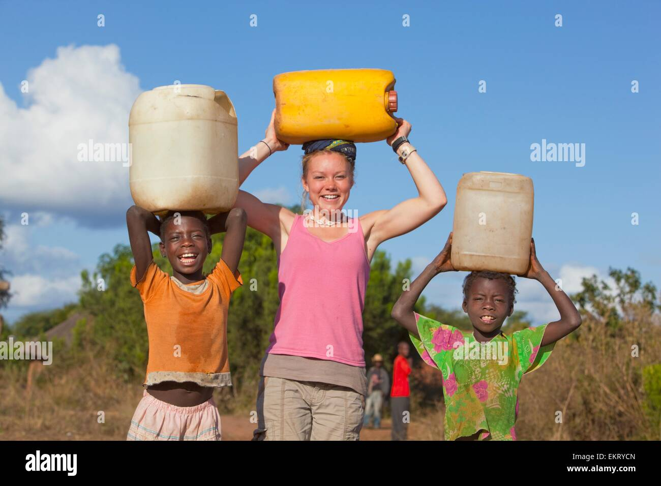 A Young Women And Two Children Hold Water Jugs On Their Heads; Manica, Mozambique, Africa - Stock Image