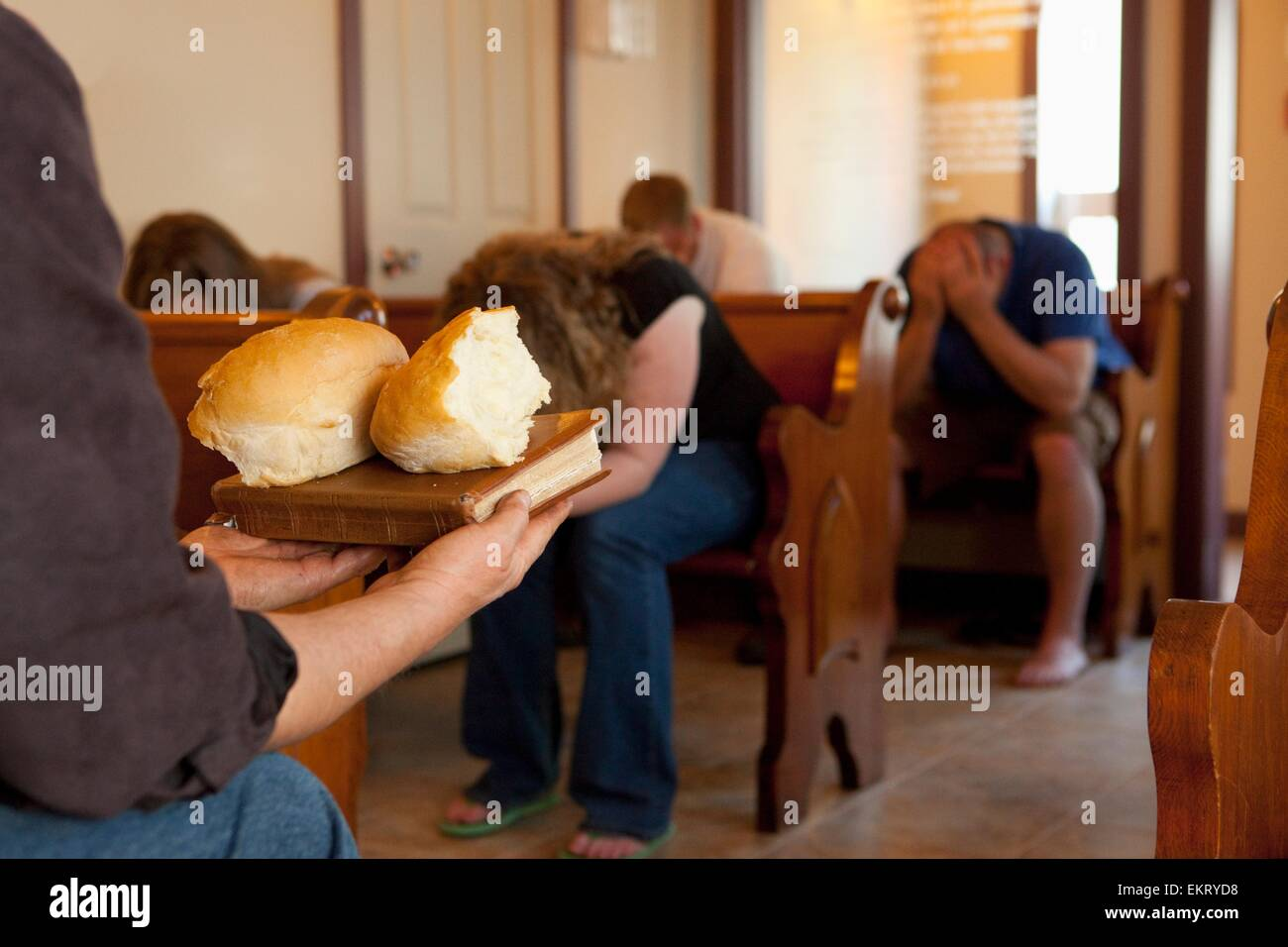 A Group Of People With Heads Bowed Ready To Take Bread For Communion; Manica, Mozambique, Africa - Stock Image