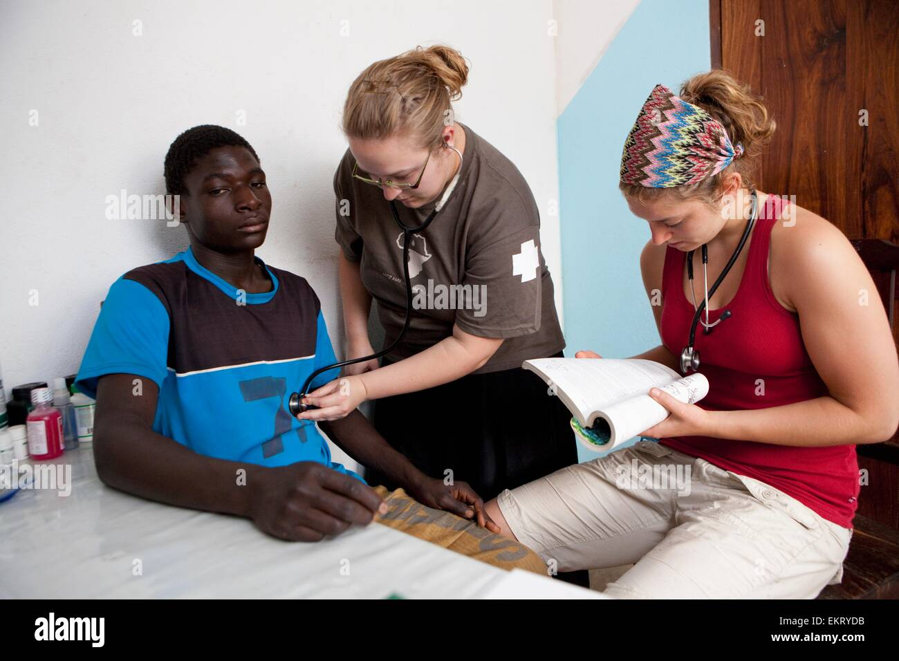 Medical Team Does A Check Up On A Young Man; Manica, Mozambique, Africa - Stock Image