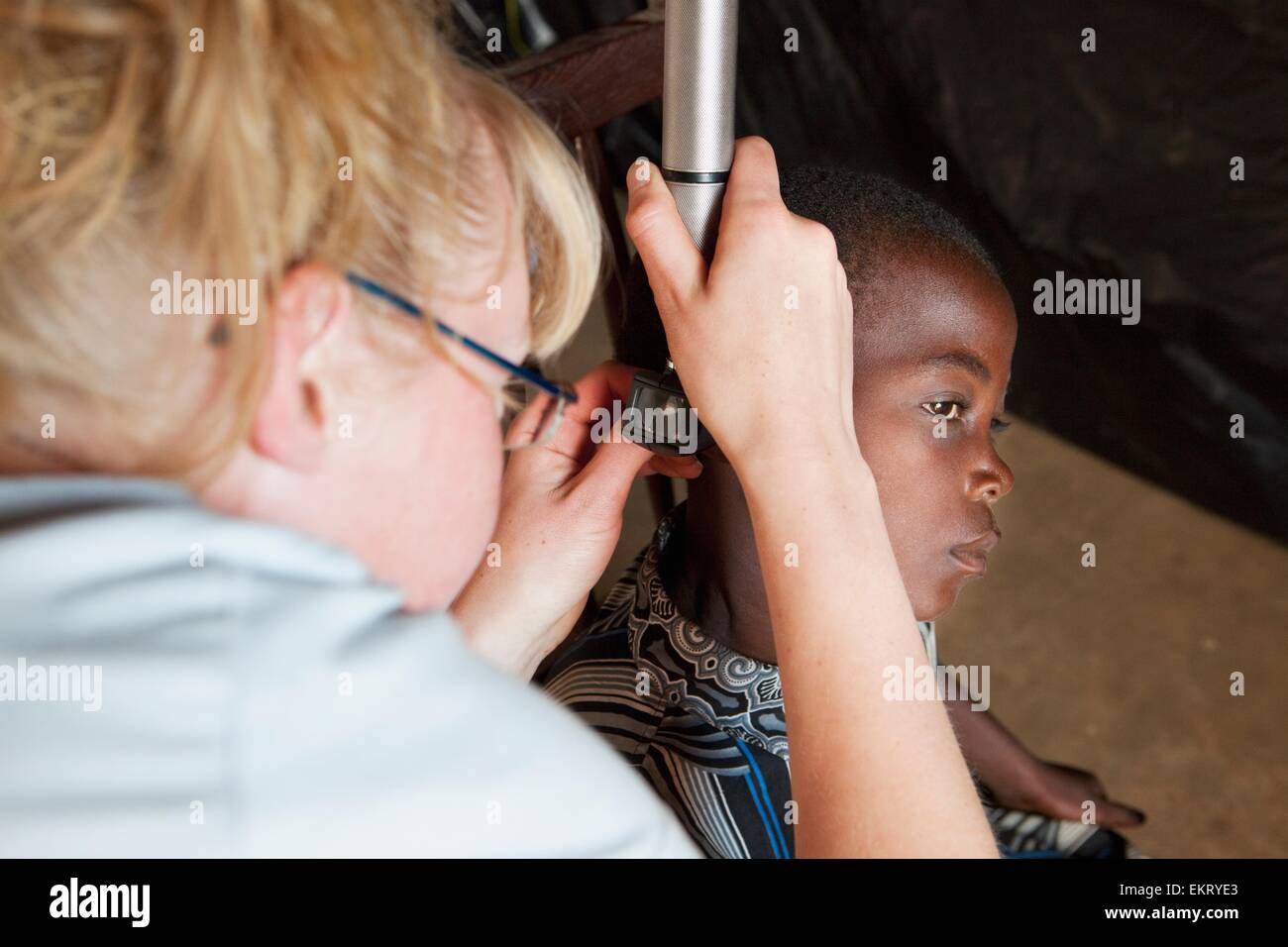A Nurse Checking A Child's Ears; Manica, Mozambique, Africa - Stock Image