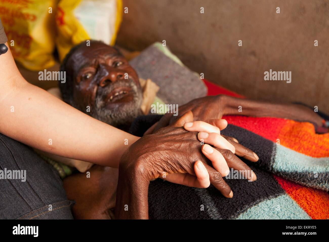 A Nurse Holds The Hand Of A Man Dying Of Pneumonia; Manica, Mozambique, Africa - Stock Image