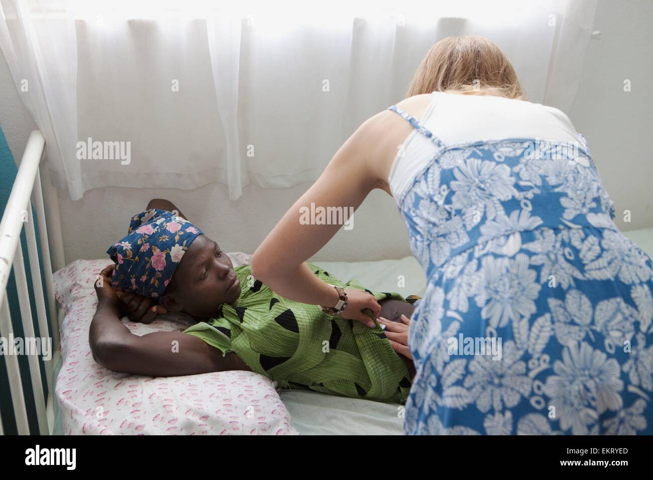 A Girl Being Cared For By A Medical Worker; Manica, Mozambique, Africa - Stock Image