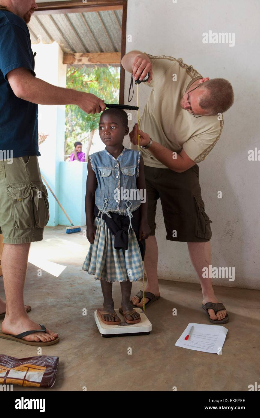Medical Workers Measuring Height And Weight Of A Young Girl; Manica, Mozambique, Africa - Stock Image