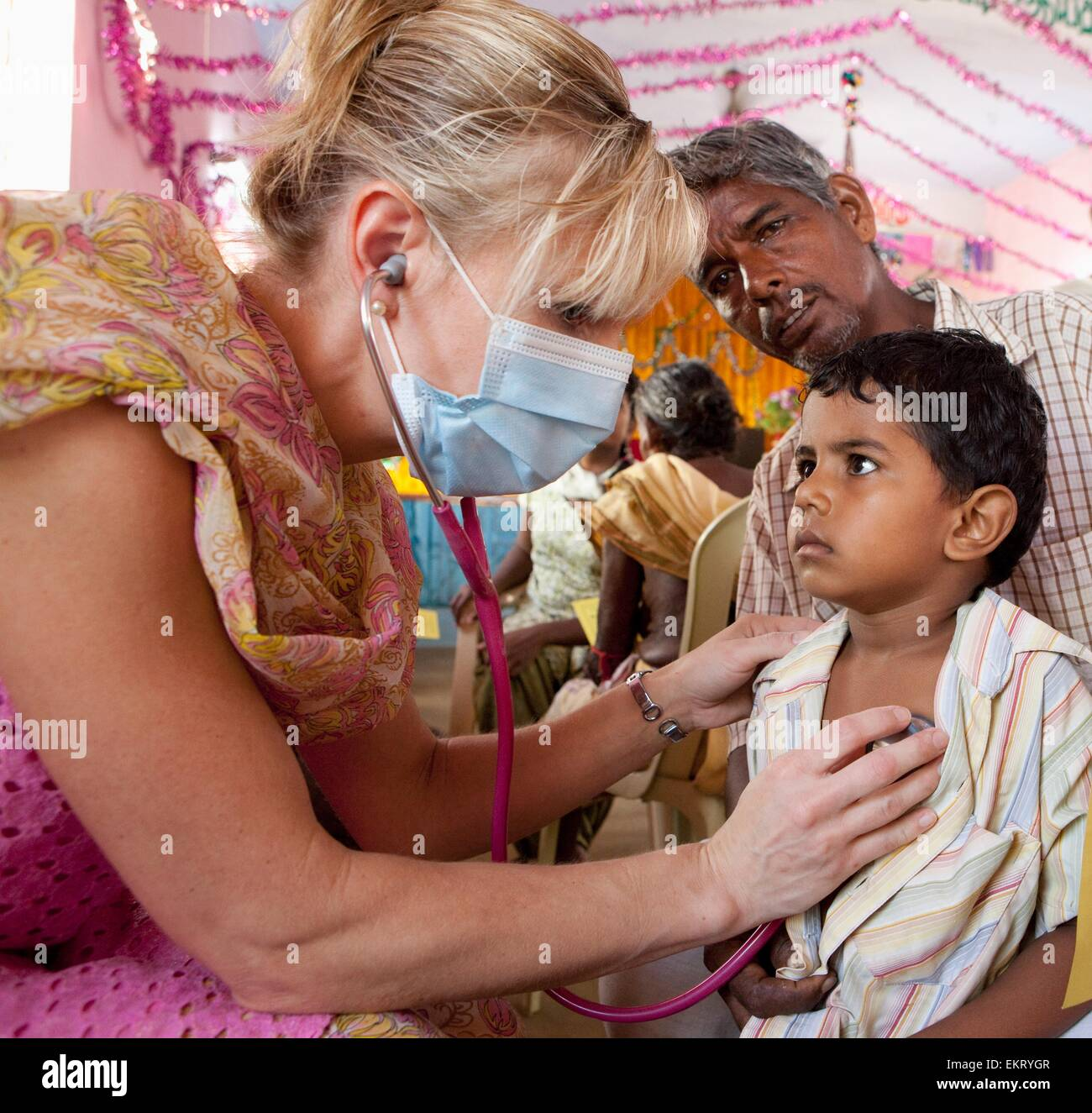 A Woman Wearing A Mask Using A Stethoscope On A Boy With His Father; Sathyamangalam, Tamil Nadu, India - Stock Image
