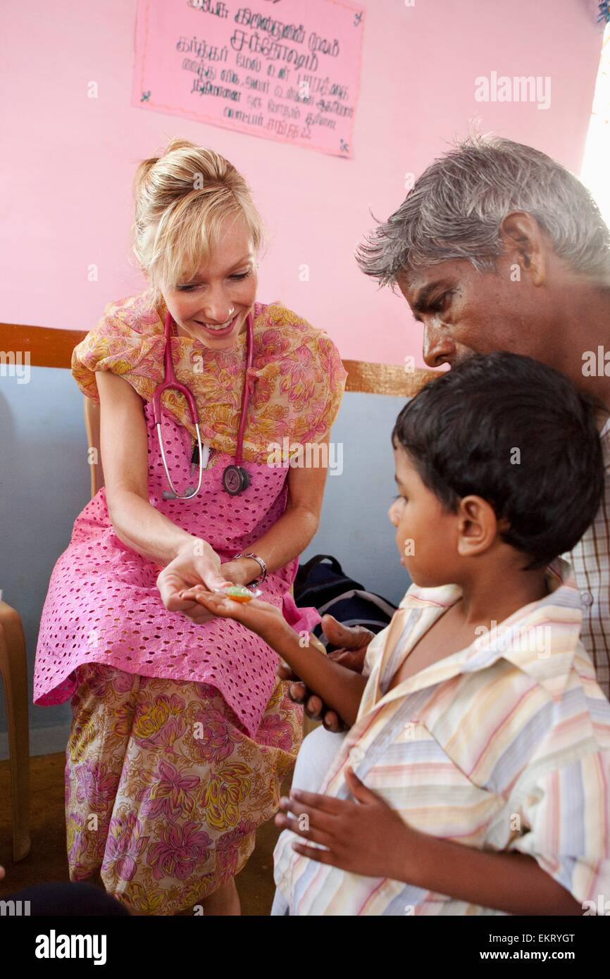 A Woman With A Stethoscope Giving A Boy A Treat After A Check Up; Sathyamangalam, Tamil Nadu, India - Stock Image