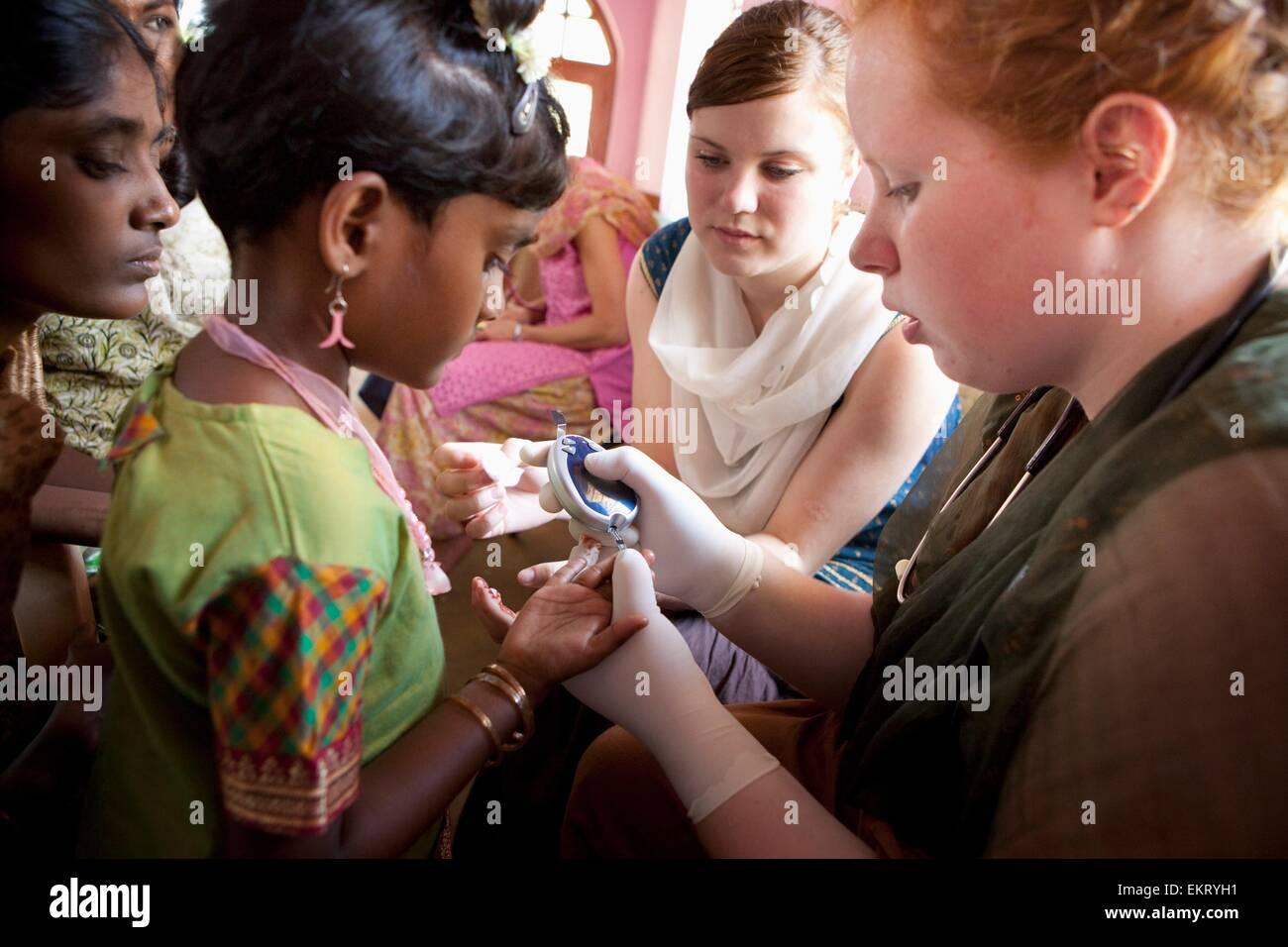 A Nurse Checks The Blood Sugar Level Of A Girl With Diabetes; Sathyamangalam, Tamil Nadu, India - Stock Image