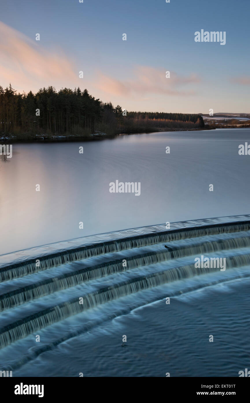 Winter sunset at Fewston Reservoir, with the overflow in the foreground. Stock Photo