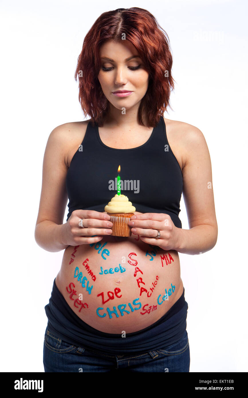 A Pregnant Woman With Names Written All Over Her Bare Belly Holding A Cupcake With A Lit Candle; Edmonton Alberta - Stock Image