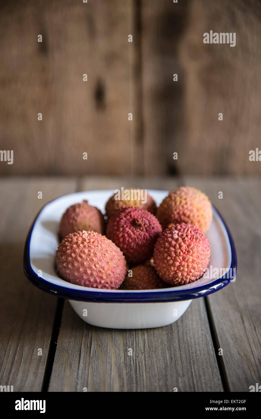 Lychees in rustic setting with wooden background - Stock Image