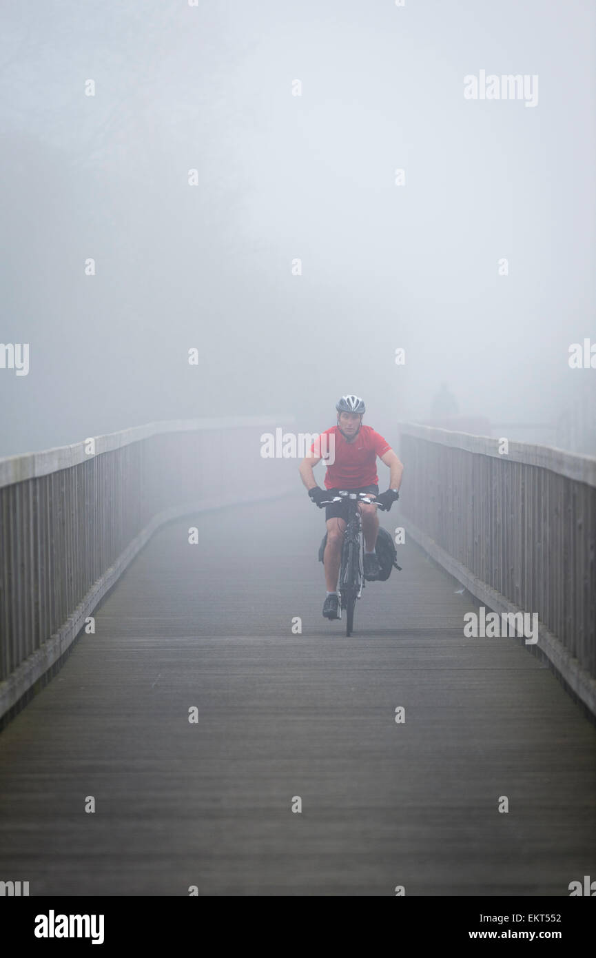 Exeter, Devon, UK. 14th Apr, 2015. Cyclists commuter through the fog on the Exe Estuary Trail near Exeter, Devon. - Stock Image