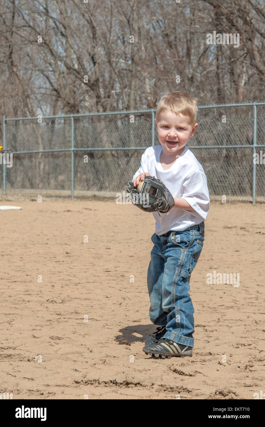 boy portrait  playing catch on baseball field with ball and glove - Stock Image