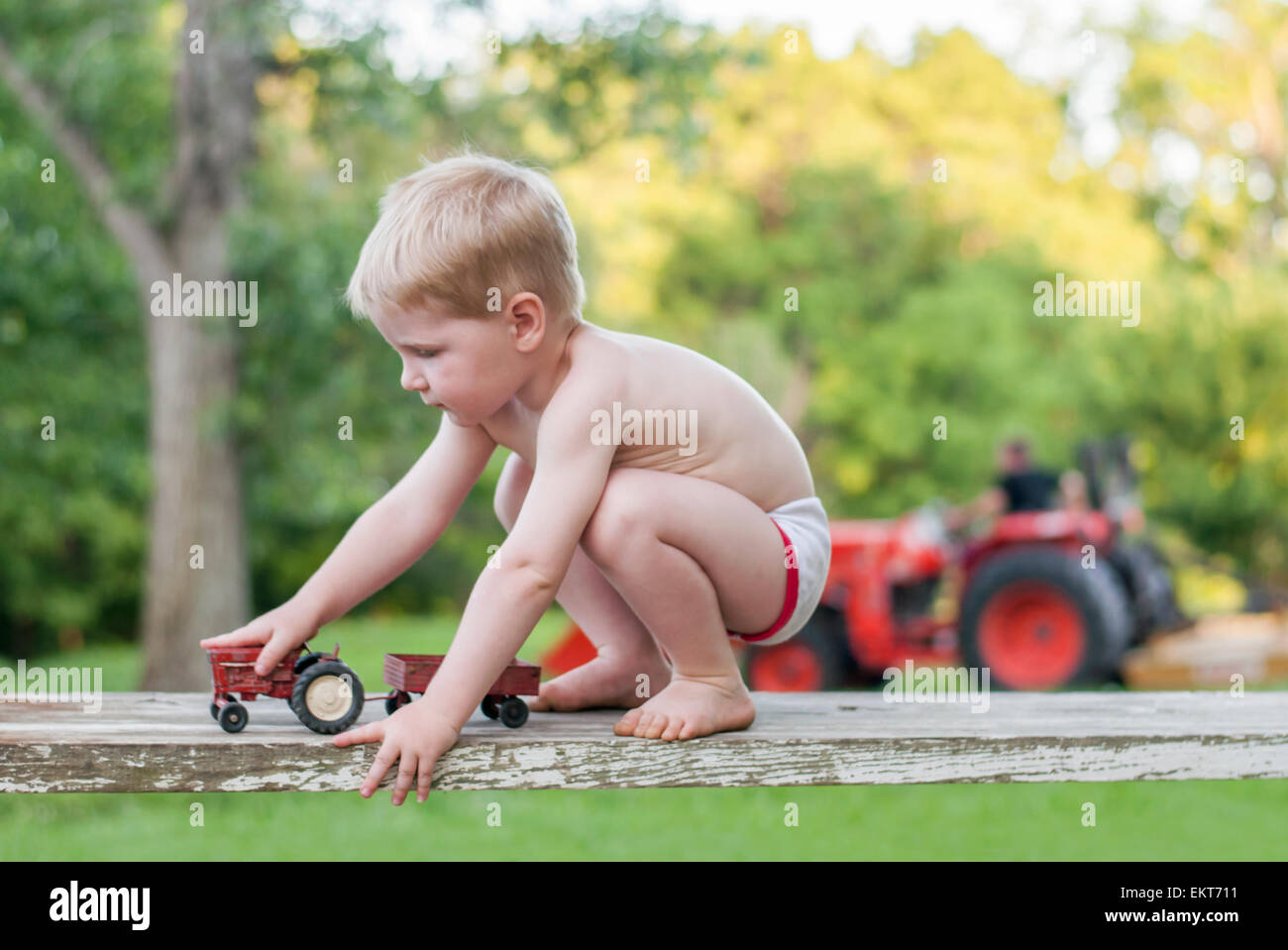 boy plays tractors farmer in background - Stock Image