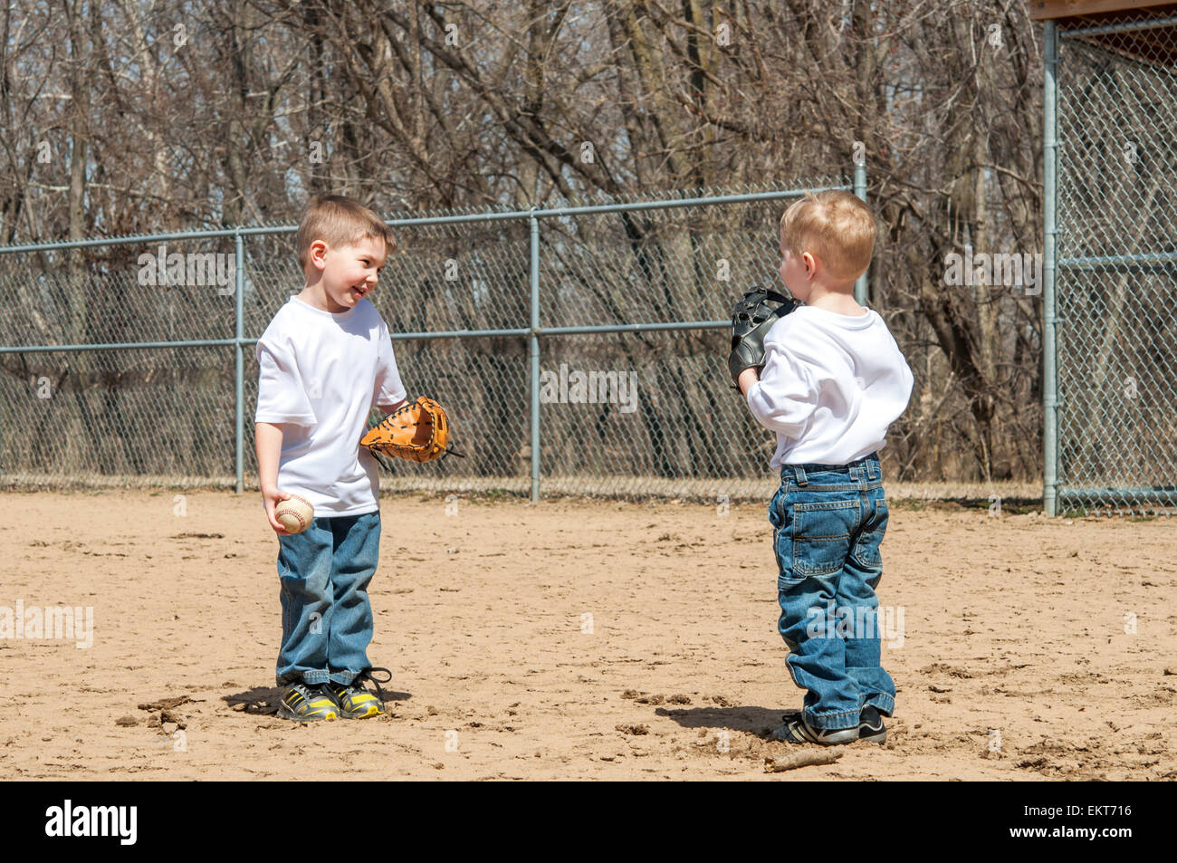 Two boys playing baseball catch and talking - Stock Image
