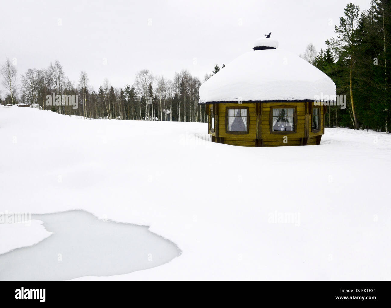 Lapland, Scandinavia, a snow covered wooden sauna shed, in a landscape of snow - Stock Image