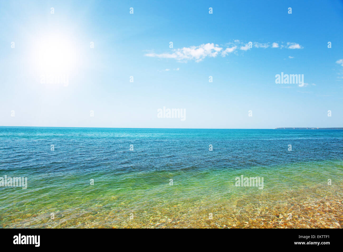 beautiful sea and cloudy sky with sun - Stock Image