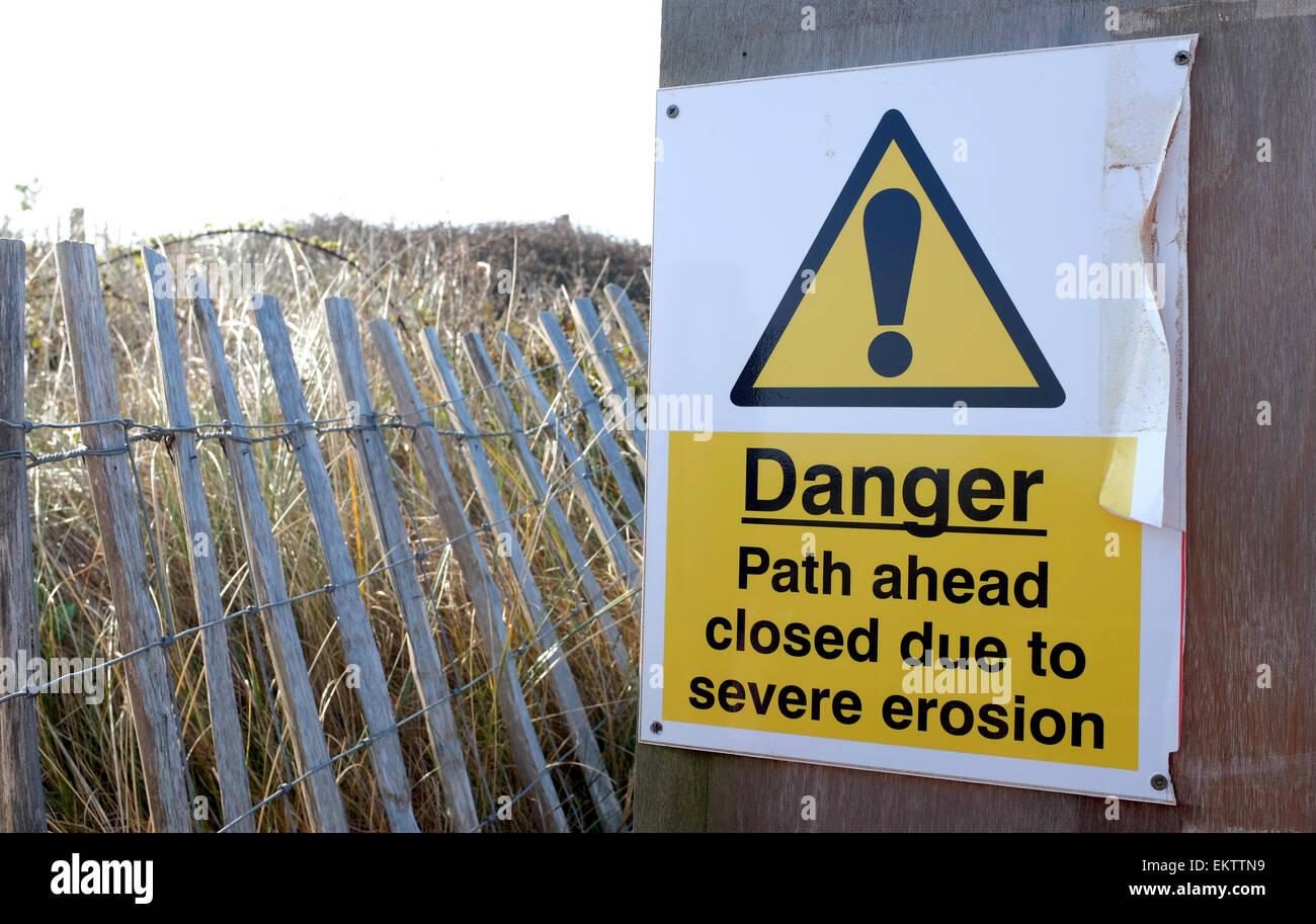 erosion danger sign in Dawlish Warren Devon after the footpath was destroyed by severe weather storms - Stock Image