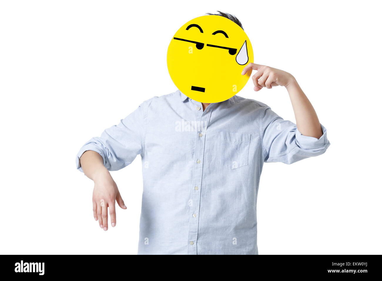 Young man with a embarrassed emoticon face in front of his face - Stock Image