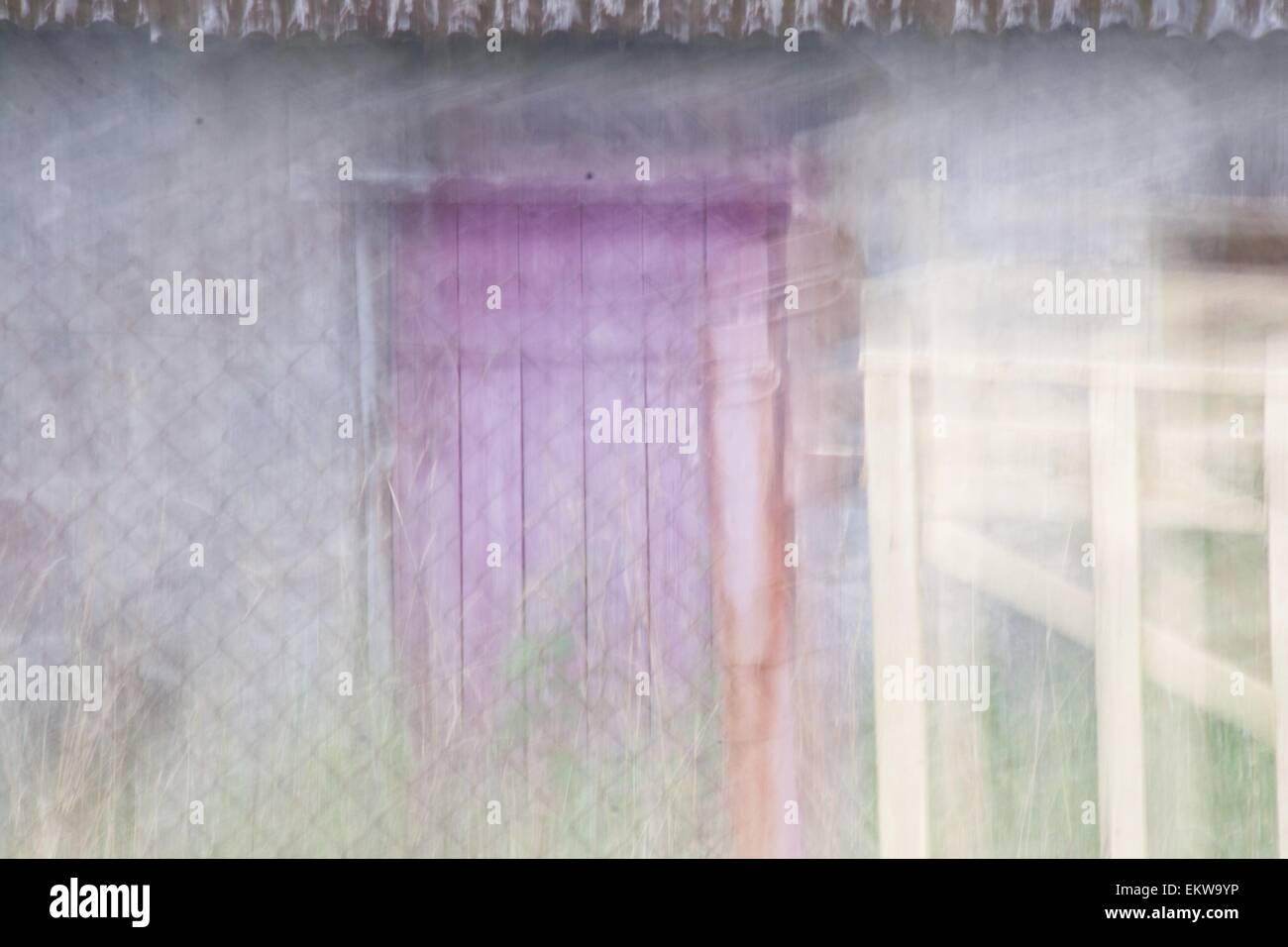 Purple door in the fog - Stock Image