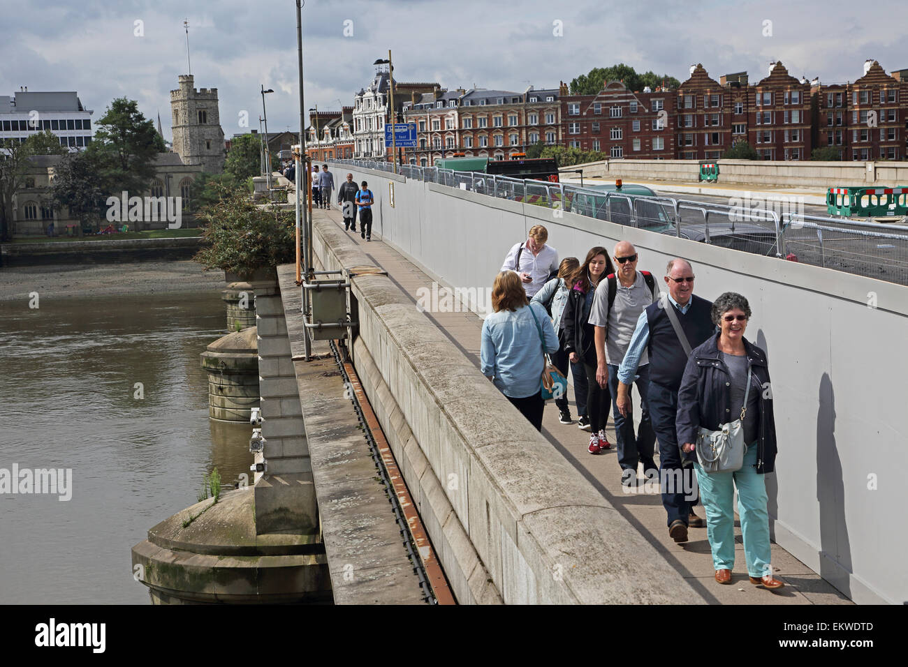 Pedestrians segregated from construction work by a temporary hoarding on Putney Bridge, west London. Bridge closed - Stock Image