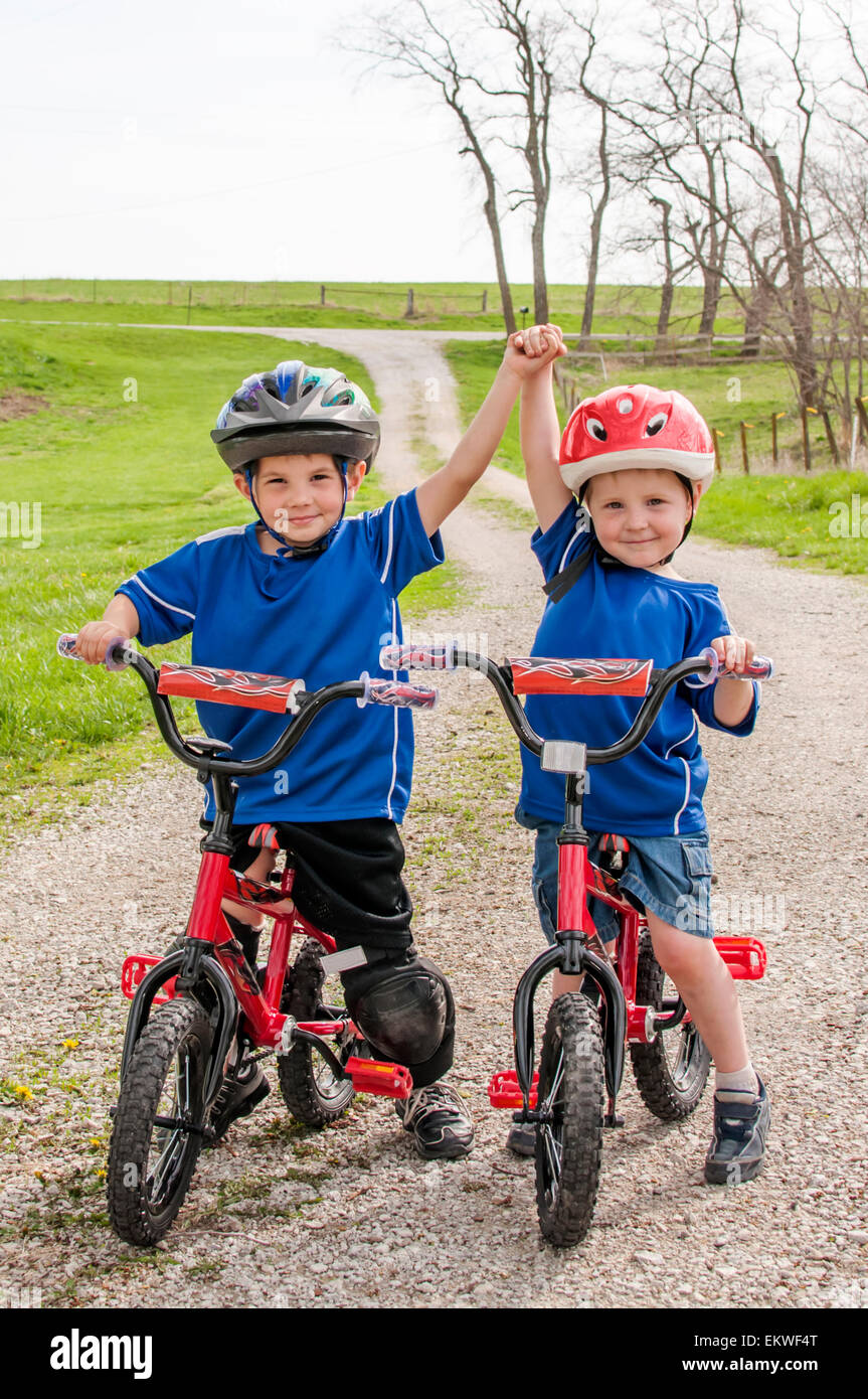 Two boys with helmets on matching bikes - Stock Image