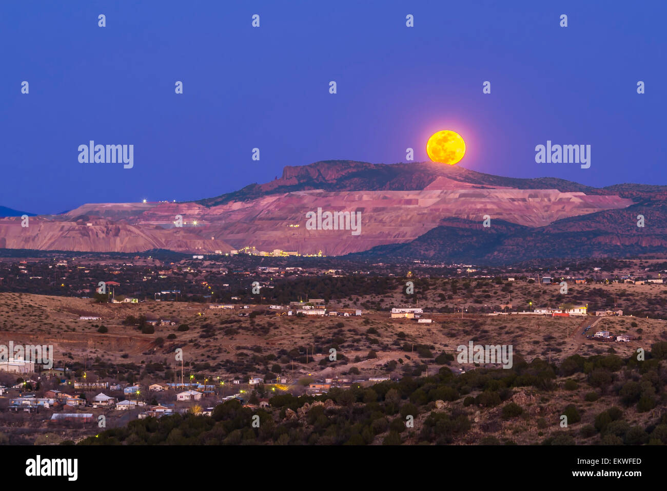 The March 5, 2015 mini-moon rises over the Santa Rita Copper Mine and cliff formation known locally as the Kneeling Stock Photo