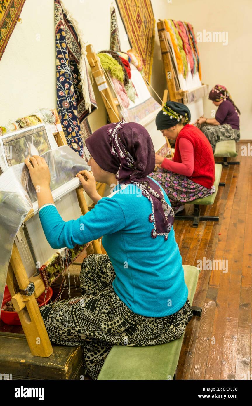 Turkish women weaving traditional hand made rugs, near Antalya, Mediterranean region, Turkey - Stock Image