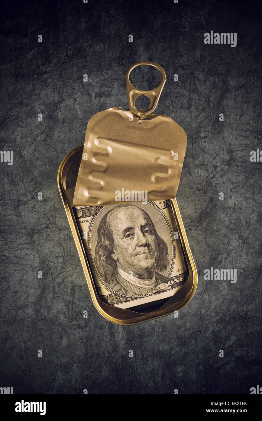 Hundred American Dollar Bill in Open Empty Sardine Fish Tin Can on Grunge Gray Background, Top View - Stock Image