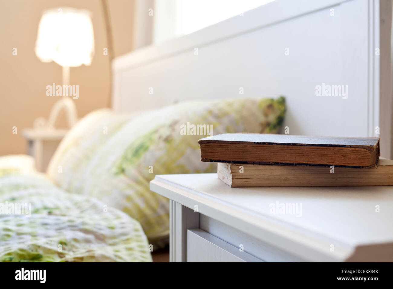 bedroom with books on nightstand - Stock Image