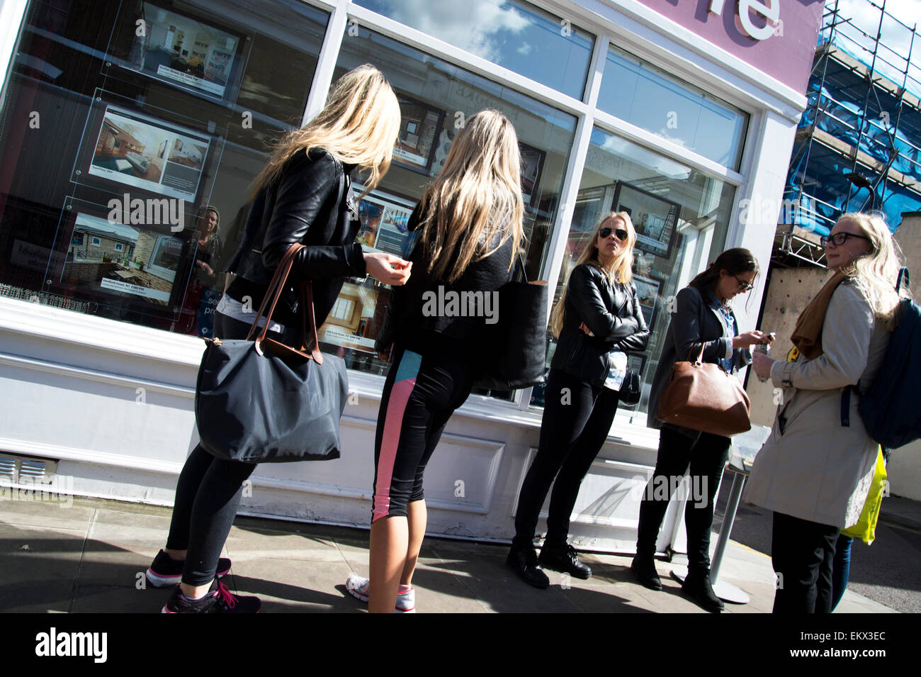 Hackney Spring 2015. Broadway market. Estate agents and blondes - two young women inspect photos of houses - Stock Image