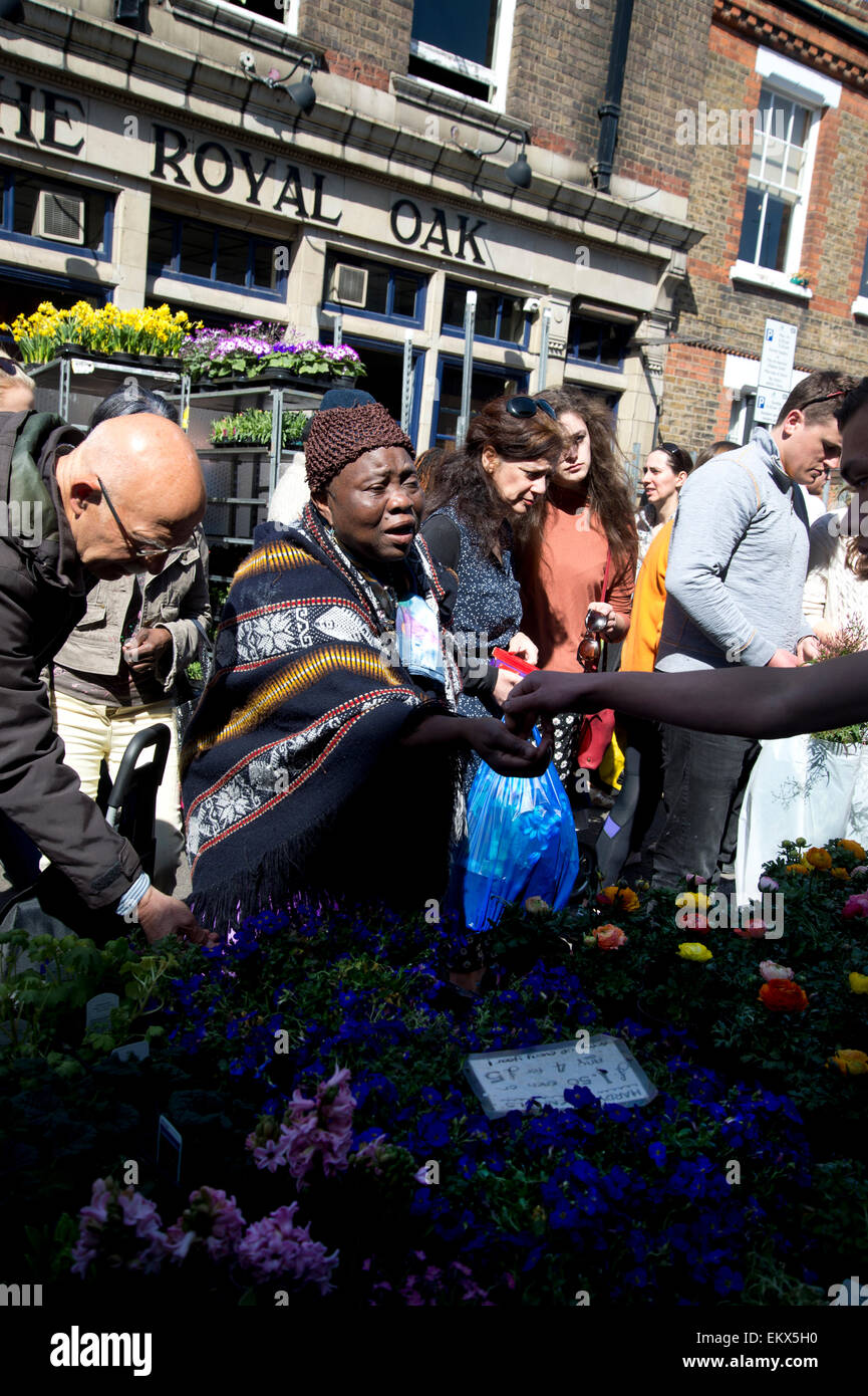 Columbia Road Sunday flower market, Spring 2015. Customers choose plants in front of the Royal Oak pub. - Stock Image