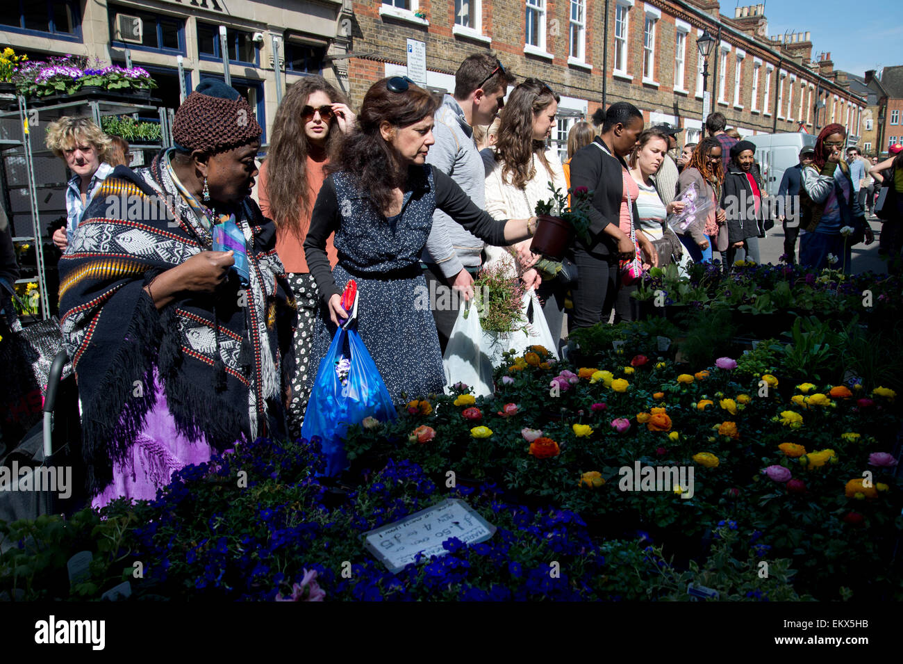 Columbia Road Sunday flower market, Spring 2015. Customers choose plants. - Stock Image