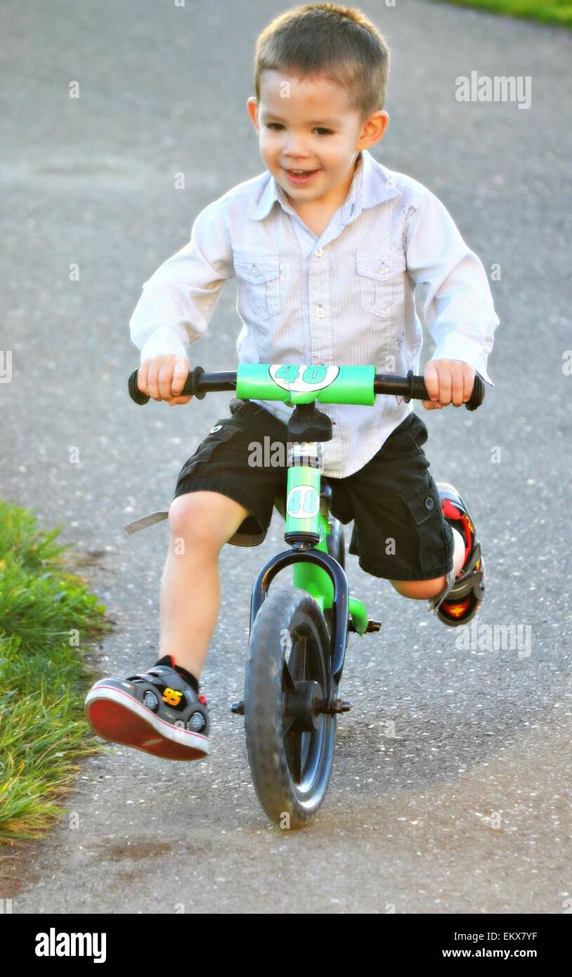 f9322a789eb Happy brown eyed 3 year old boy riding his strider bike Stock Photo ...