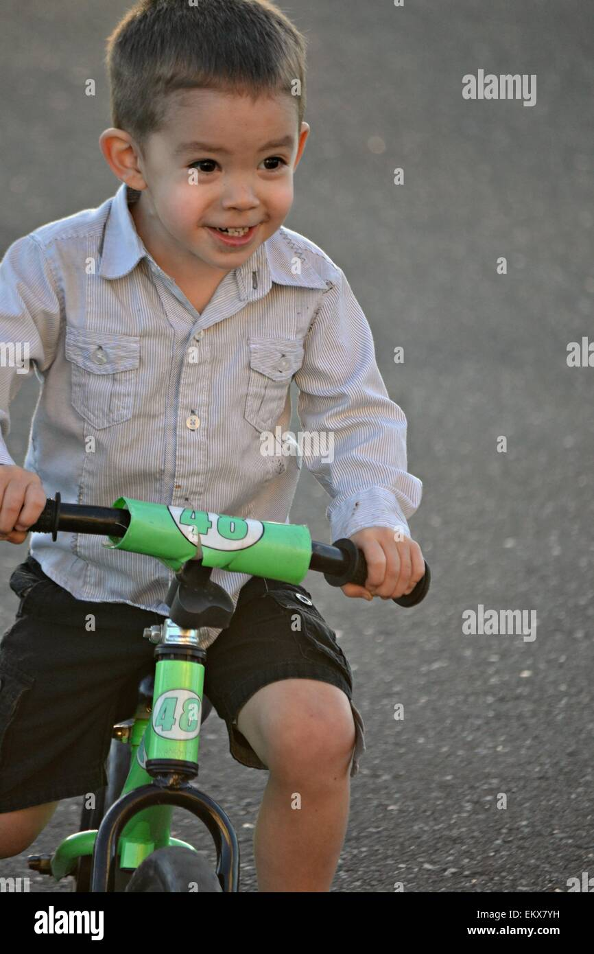 5be6af5c9a1 Happy smiling 3 year old boy riding his strider bike. - Stock Image