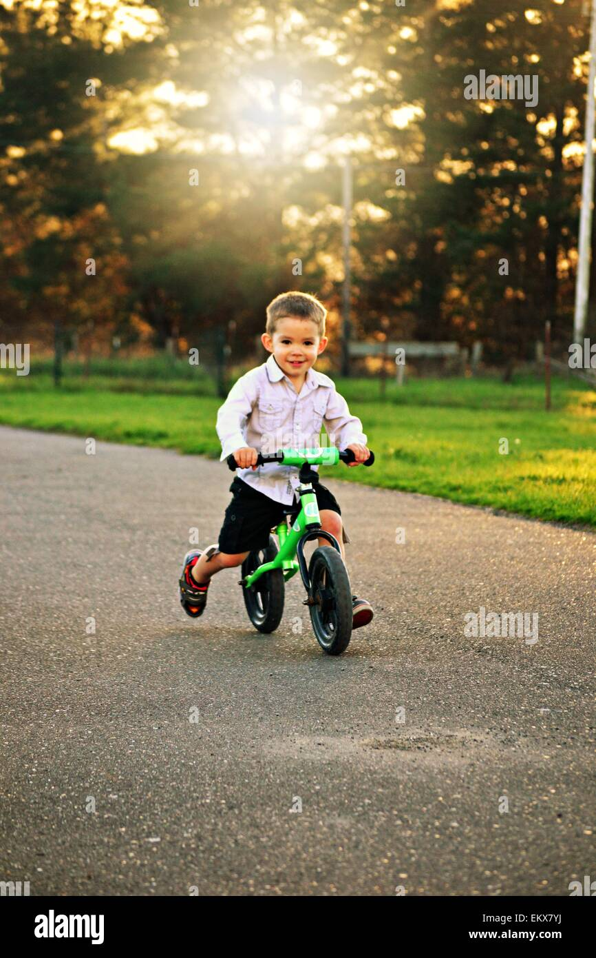2de097e8c40 Cute 3 year old boy riding his strider bike in the evening sunshine. - Stock